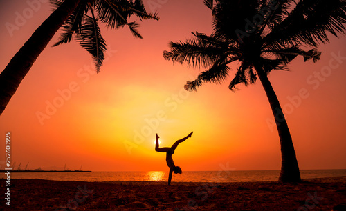 Leinwanddruck Bild Beautiful young woman practic yoga at the beach. Early morning exercise. Sunrise