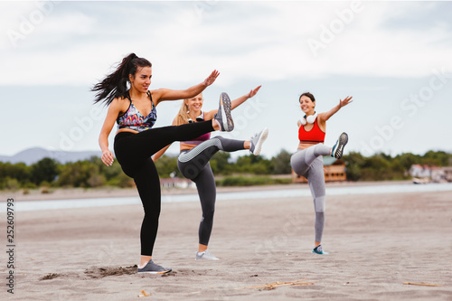 Leinwandbild Motiv Group of young women is warming up before jogging on the beach by the sea