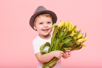 Adorable smiling child with spring flower bouquet looking at camera isolated on pink. Little toddler boy in hat holding yellow tulips as gift for mom