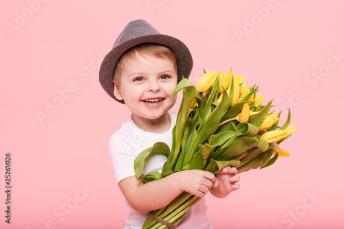 Leinwandbild Motiv Adorable smiling child with spring flower bouquet looking at camera isolated on pink. Little toddler boy in hat holding yellow tulips as gift for mom
