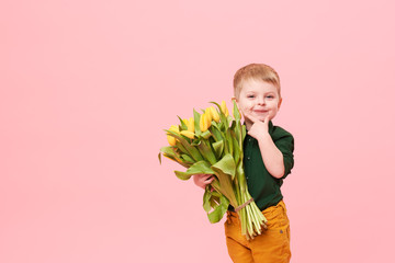 Adorable smiling child with spring flower bouquet looking at camera isolated on pink. Little toddler boy holding yellow tulips as gift for mom. Copy space for text on left side