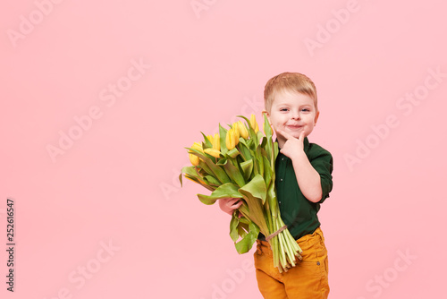 Adorable smiling child with spring flower bouquet looking at camera isolated on pink. Little toddler boy holding yellow tulips as gift for mom. Copy space for text on left side - 252616547