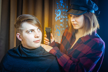 Electric clipper. The girl is cutting a young man. The hairdresser. Men's haircut. Married couple. Haircut.
