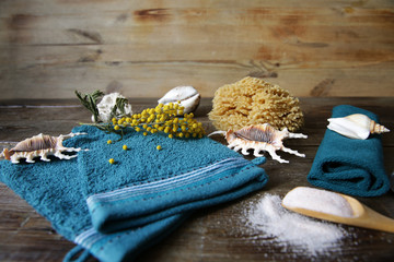 terry massage and spa mittens, salt in a wooden spoon, towel, shells and flowers for decoration with copy space for text