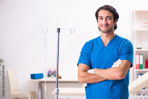 Leinwanddruck Bild Young male doctor in blood transfusion concept