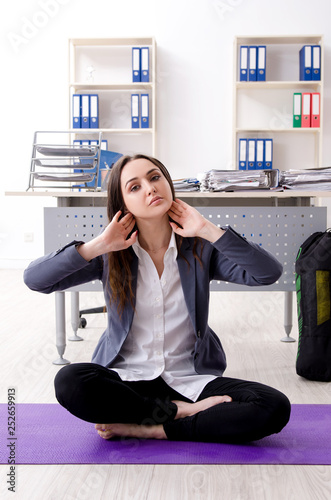 Female employee doing sport exercises in the office  - 252659913