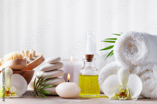 Spa, beauty treatment and wellness background with massage pebbles, orchid flowers, towels, cosmetic products and burning candles. © juliasudnitskaya