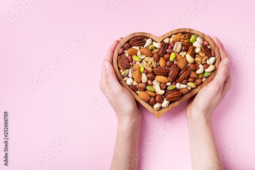 obraz lub plakat Womans hands holding heart shaped bowl with mixed nuts on pink table top view. Healthy food and snack. Flat lay.
