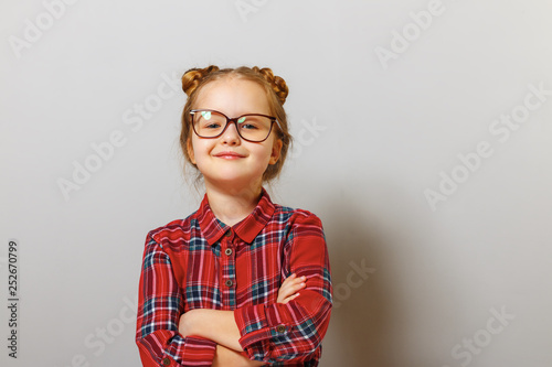 Portrait of a funny little preschool child girl in glasses on gray background. Education. Back to school.