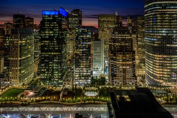 Golden lights of the San Francisco skyline and Salesforce Transit Center Park at the bottom