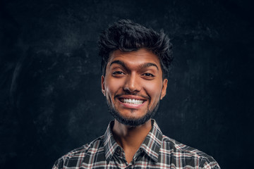Close-up portrait of a handsome Indian man wearing a plaid shirt, smiling and looking at a camera. Studio photo against a dark textured wall