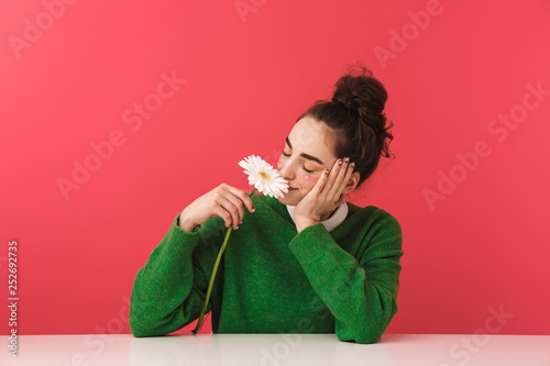 Pretty nerd girl sitting at the table isolated
