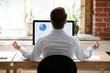 Leinwanddruck Bild - Rear view businessman sitting at desk opposite pc doing yoga
