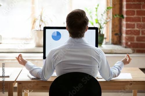 Leinwanddruck Bild Rear view businessman sitting at desk opposite pc doing yoga