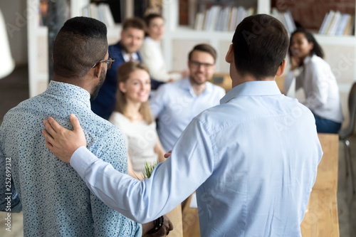 Leinwandbild Motiv Boss introducing black new worker to workmates