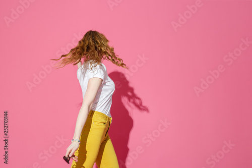 Trendy party mockup. Cheerful blonde woman in white T-shirt and trendy yellow jeans dancing on pink background. - 252703144