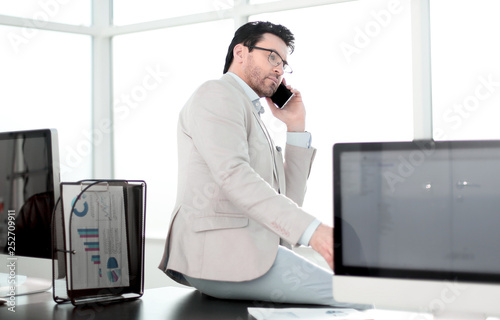 serious businessman talking on smartphone sitting on his desktop