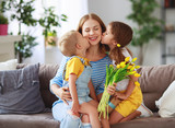 Happy mother's day! Children congratulates moms and gives her a gift and flowers .