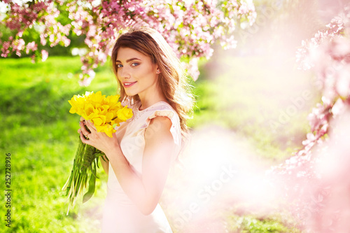 Beauty Portrait of Beautiful Young Brunette Woman In Nice Spring Dress With A Bouquet Of Tulips.Spring Style. Beautiful Spring Garden. Fashion Spring Summer Photo. Fashion and style concept. Long edge - 252728936