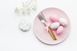 Easter dining table in pastel colors. Plate, cutlery, painted eggs, gingerbread and dry flower branch on white background top view space for text