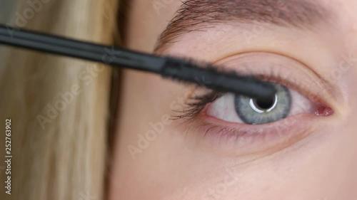 Close up of putting mascara on lashes of female blue eye