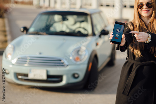 Leinwandbild Motiv Woman using Smartphone near the car. Mobile phone apps for car owners concept.