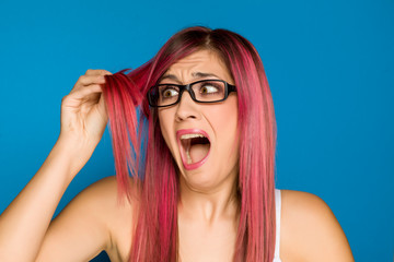 young shocked woman with pink hair on blue background © vladimirfloyd