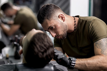 Handsome barber in black gloves trims a beard of stylish man at a barbershop