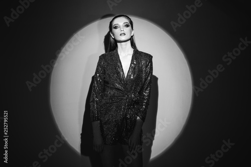 Black and white portrait of trendy girl with hair pulled back and stylish makeup in a shining dress standin g next to the wall in bright spotlight