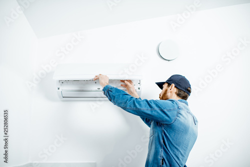 Repairman in blue workwear serving the air conditioner changing filter on the white wall background - 252806535