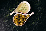 Close up of raw olives and oil at two red plate pear shape. Healthy and organic green olives fruits on dark marble background.