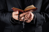 Hands of a christian priest dressed in black holding a crucifix and reading New Testament book. Religious person studies Bible and holds prayer beads, low-key image