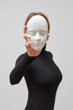 Leinwandbild Motiv Young woman in a black sweater with plaster mask in her hand instead of face on a white background. Concept The masks we wear