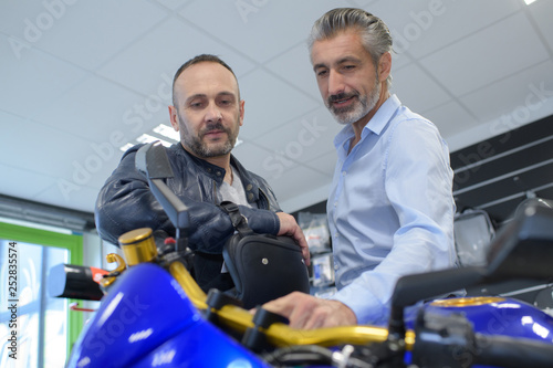 portrait of positive mechanic and smiling customer chatting about motorbike