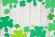 Green shamrocks on weathered whitewash textured wood background