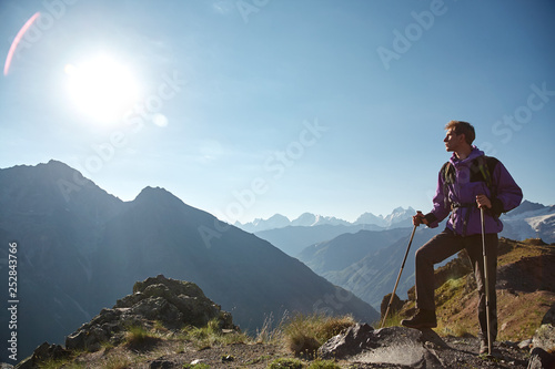 climber on trail in the mountains. a hiker in the mountain. Climb to the top - 252843766