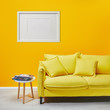 coffee table standing near modern yellow sofa near white frame hanging on wall