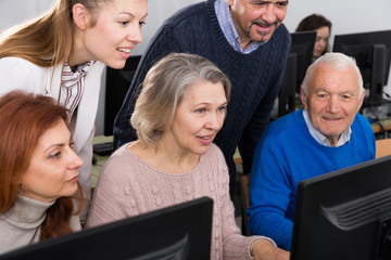 Young and mature  partners grouped around computer monitor