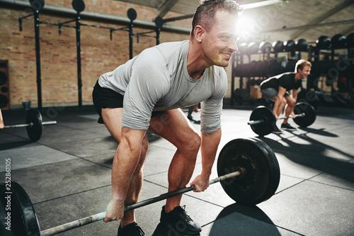 Leinwanddruck Bild Smiling man lifting heavy weights at the gym