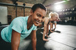 Smiling young woman doing pushups during a gym workout session