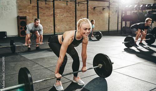 Leinwanddruck Bild Fit young woman weightlifting during a gym class