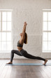 Leinwanddruck Bild - Woman practicing yoga, standing in anjaneyasana pose, Horse rider, vertical