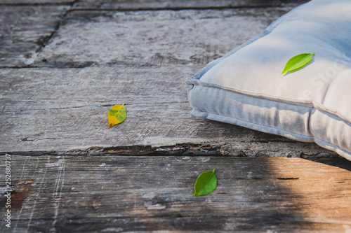 Lonely pillow in the light and shadow on the wooden floor and fallen leaves. - 252880737