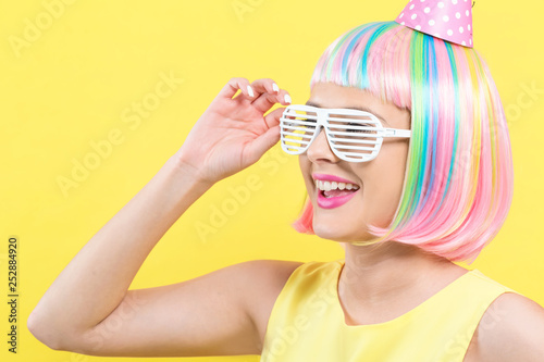 Woman in a wig with a party hat on a yellow background