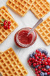 Belgian waffle with jar full of jam and decorated with fruits on a marble background viewed from above. Top view