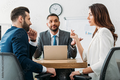 selective focus of investors in suits talking with advisor on background at workspace