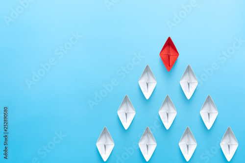 Leinwanddruck Bild Leadership concept. Red leader paper ship leading among white on blue background. copy space