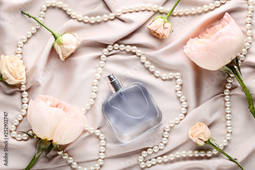 Perfume bottle with flowers and beads on satin background