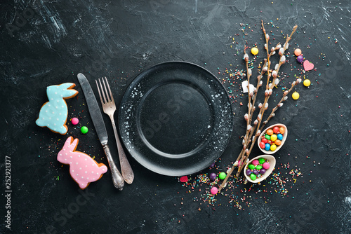 Easter greeting card. Happy Easter. Easter gingerbread cookies and decorative colored eggs. On a black background. Top view. Free copy space.