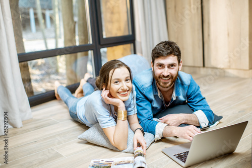 Leinwanddruck Bild Portrait of a happy couple lying on the floor with laptop and magazines, relaxing at the cozy home